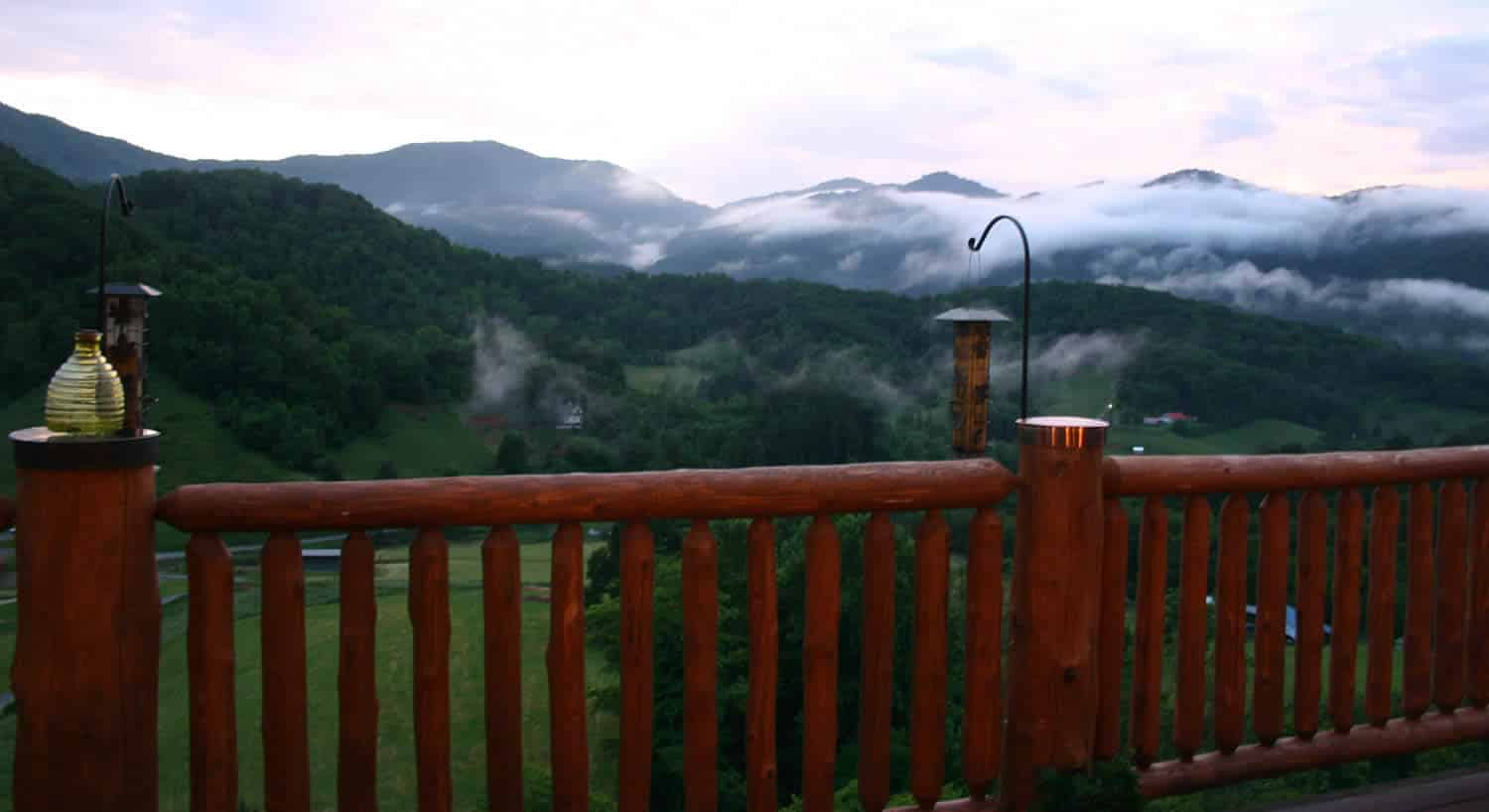 View of misty mountains and a green valley from a wooden deck with bird feeders.