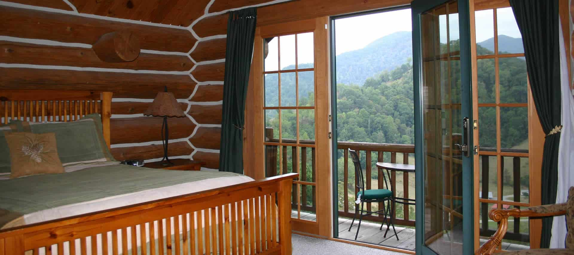 log-cabi bedroom with bed next to private balcony overlooking wooded hills.