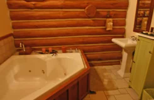 Heart-shaped whirlpool tub in bathroomw ith log-cabin walls and tile floors.