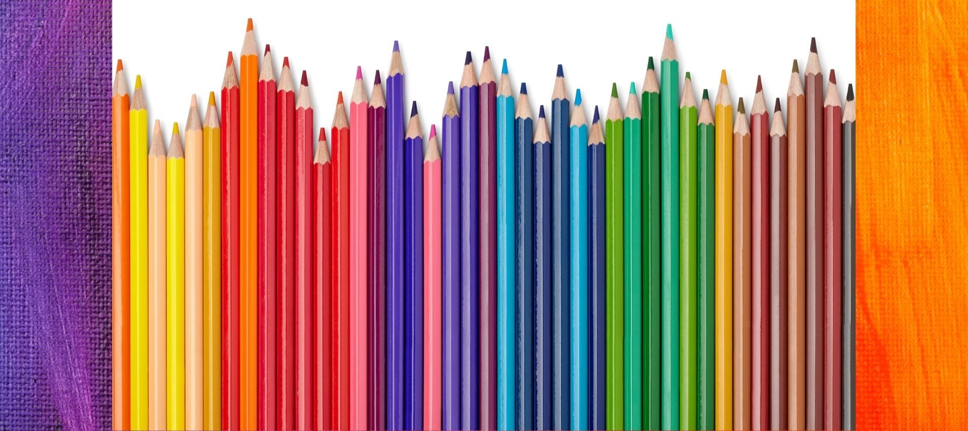 Colored pencils in a row of varying heights in a rainbow of colors
