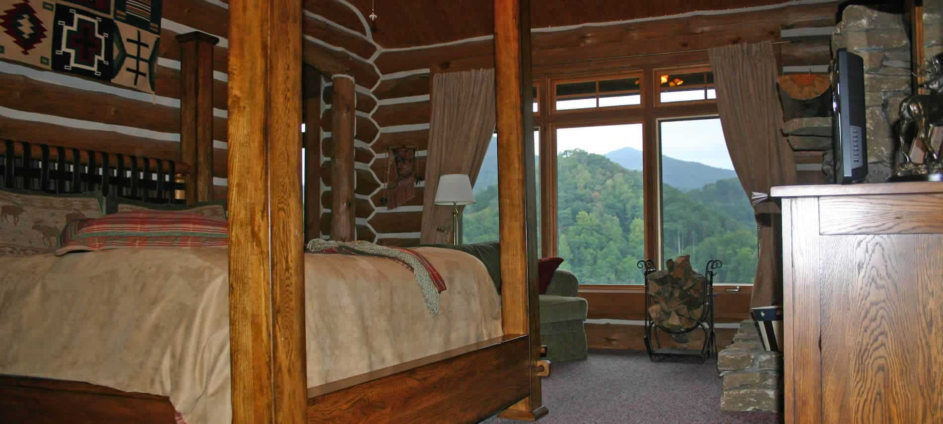 Large wooden poster bed in cozy bedroom with large windows overlooking tree-covered hills.