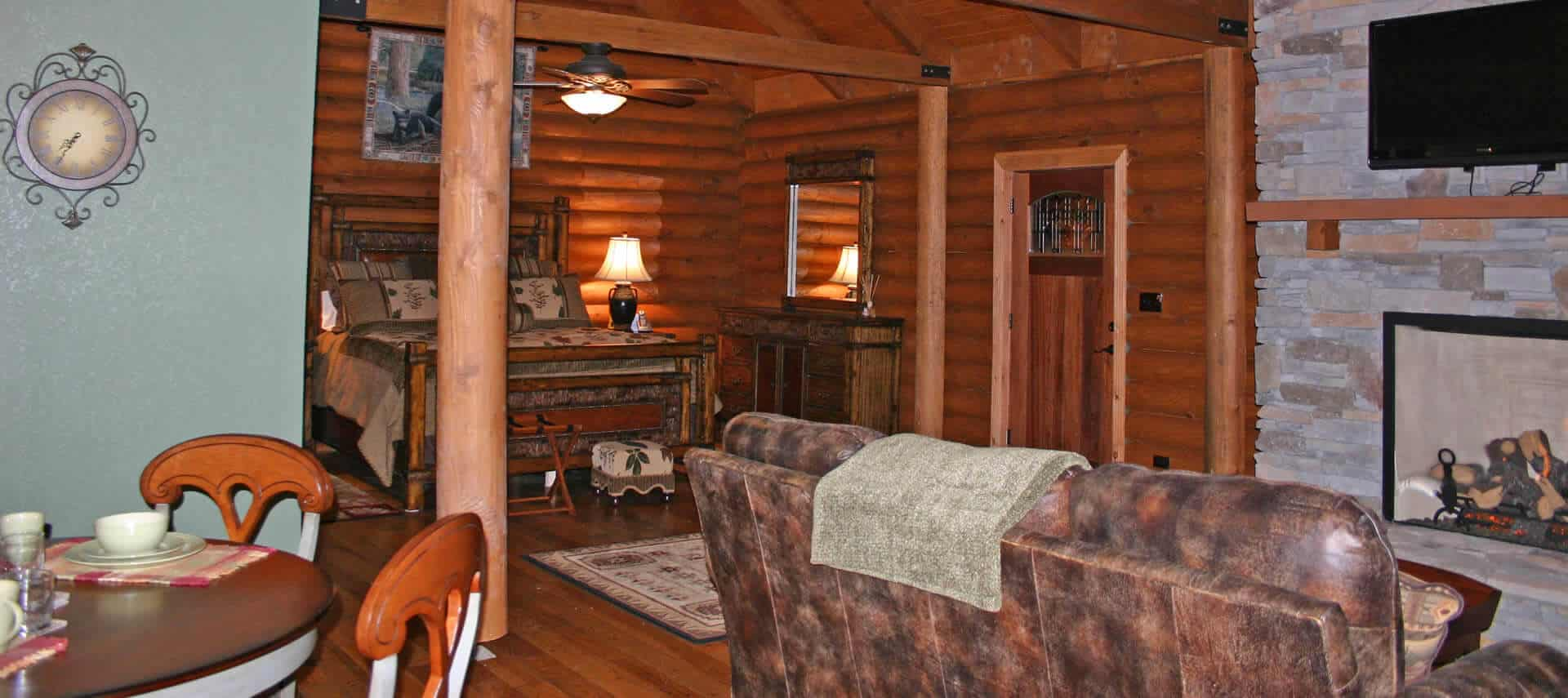 Large suite with wooden bed, log-cabin walls, a stone fireplace, leather sofa and table and chairs.
