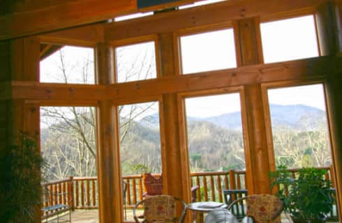 Large soaring windows overlook the mountains - inside is confortable leather furniture and wooden floors.