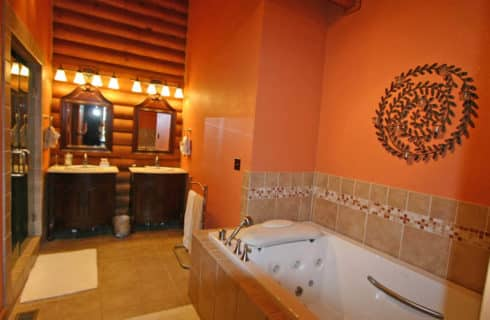 Elegant large bathroom with terra-cotta paint holds a tiled whirlpool tub, two wooden vanities with mirrors and a large shower with mirror doors.