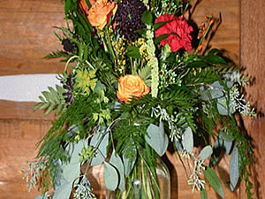 Red carnations, orange roses, allot of greenery in a large Vase