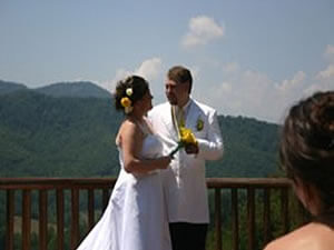 Wedding couple holding a yellow flower facing the crowd with the mountains in the background.