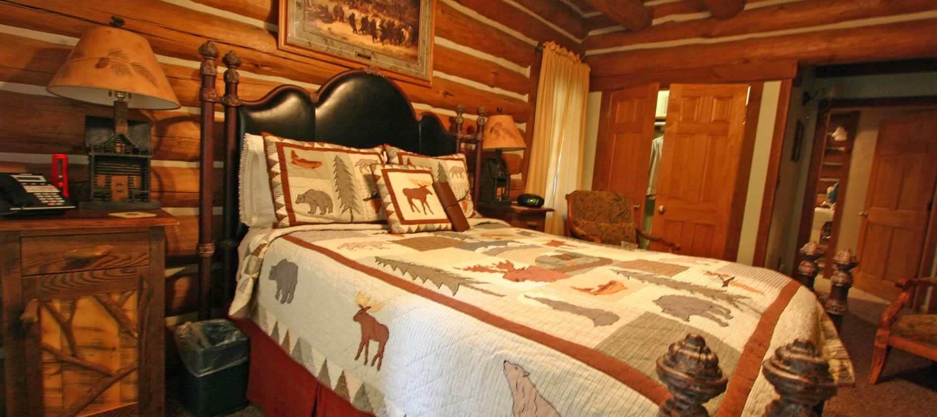 Log-cabin bedroom with large bed made up in a woods-themed quilt, two chairs and nightstands with lamps.