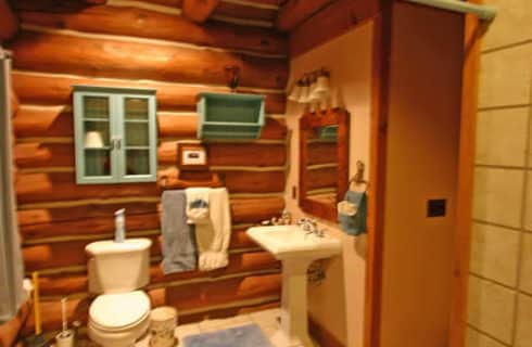 Bathroom with beige tile in an upscale log-cabin style home.