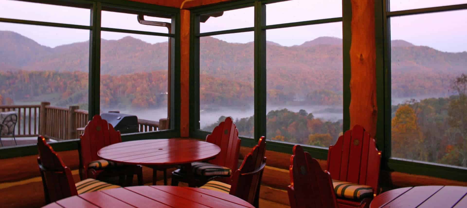 Breakfast tables with padded chairs in a room with large windows overlooking a misty mountain scene.