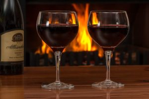 ttwo wine glasses filld with red wine with a fireplace background