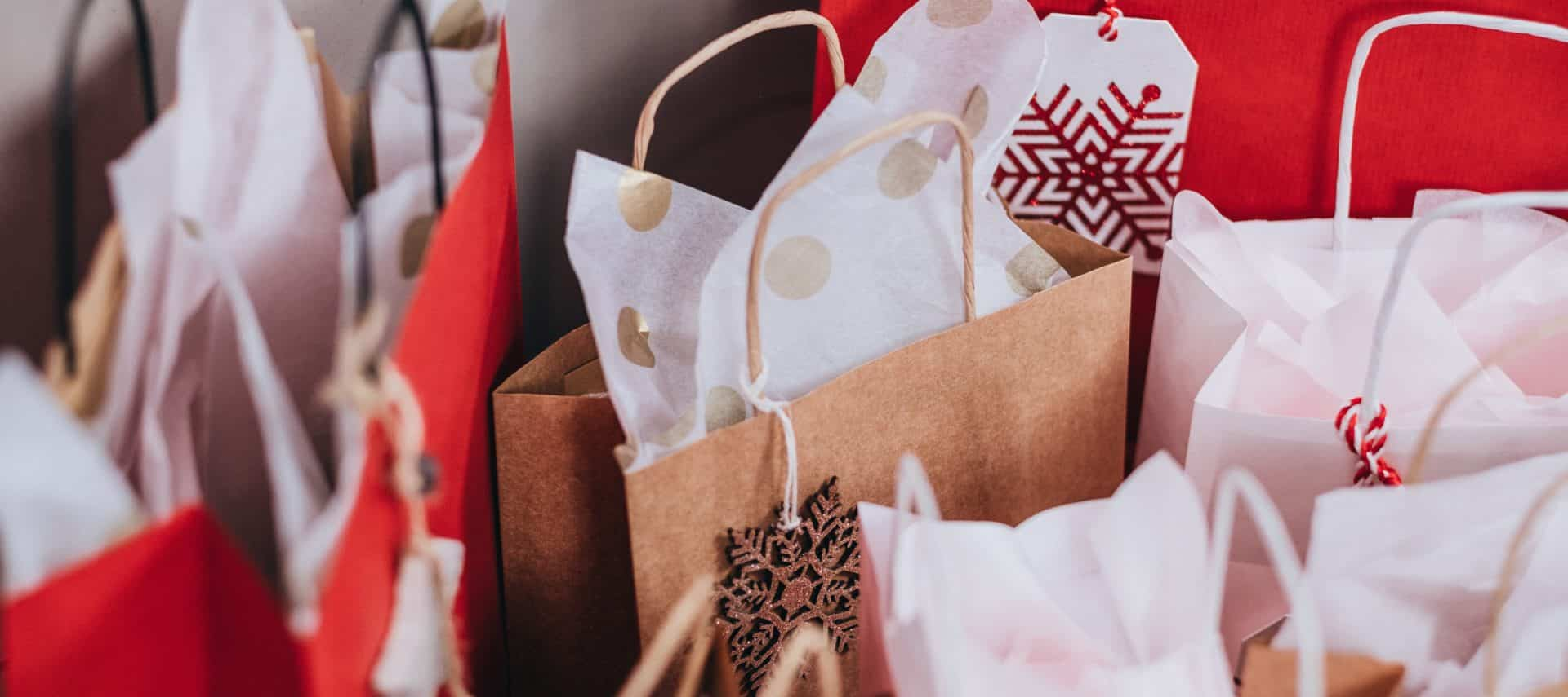 Several red and tan holiday shopping bags