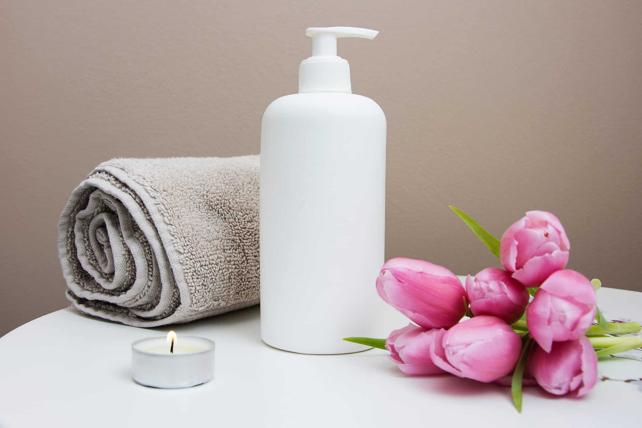 Spa table with rolled towel, lotion, candle and flower