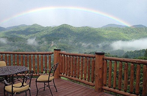 Panoramic view of mountains with blue sky and rainbow from large wood deck with black iron table and chairs