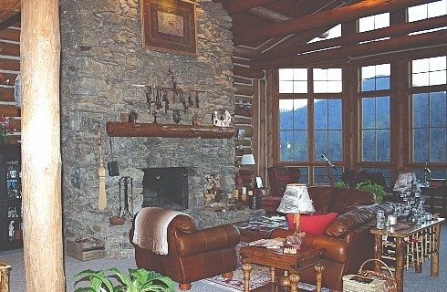 Main living room with floor to ceiling stacked stone fireplace with brown leather couch and comfortable chairs facing wall of two story windows facing mountains