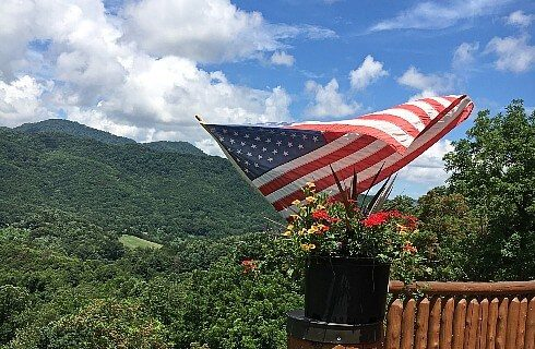 American flag waving in wind from wood deck in front of lodge facing mountain range and blue sky with some white clouds