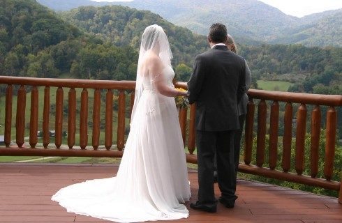 Bride in long flowing white gown with train and vail and groom in dark gray suit on wood deck facing the mountains exchanging vows