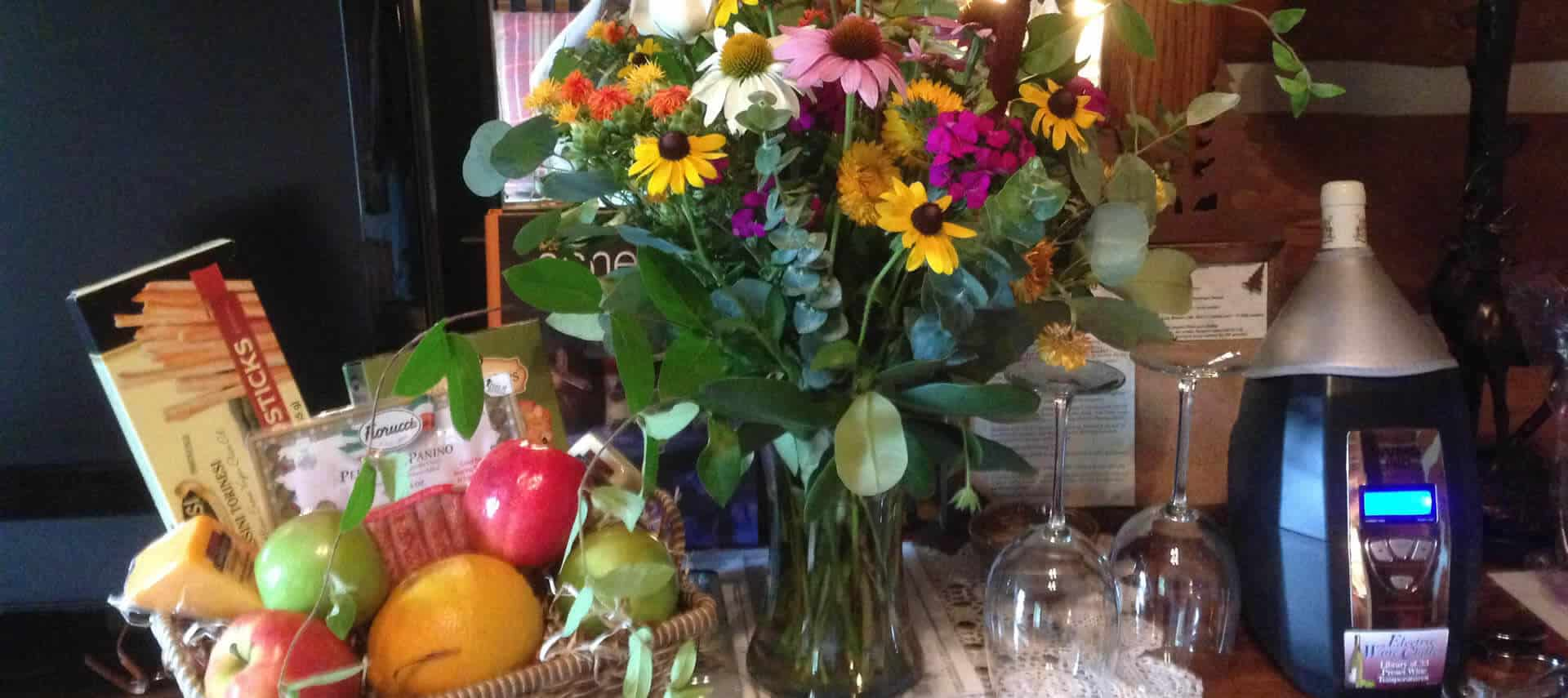 Pretty wildflowers in a glass vase next to a basket of fruit and snacks and bottle of wine in chiller.