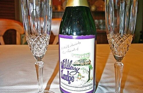Two crystal wine flutes next to Wildberry Lodge bottle of wine on wood table and white napkins