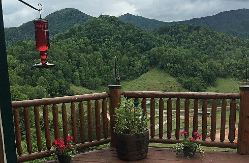 Wide view of green tree covered hills and mountain range in background from large wooden deck with red bird feeder