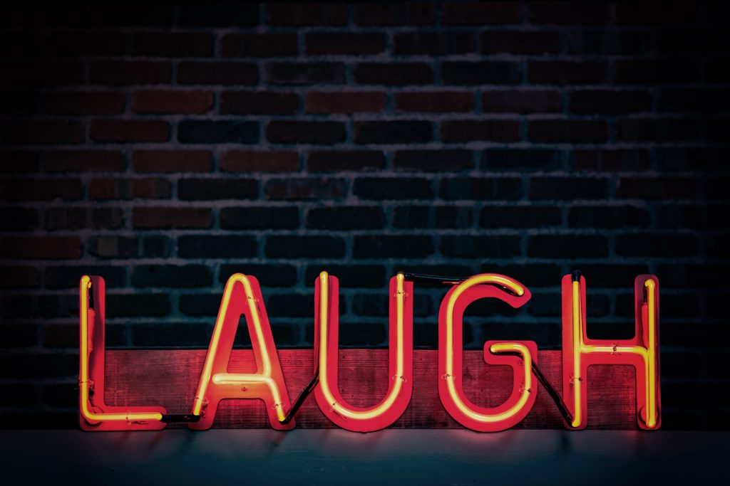 """Red neon sign that says, """"LAUGH"""""""