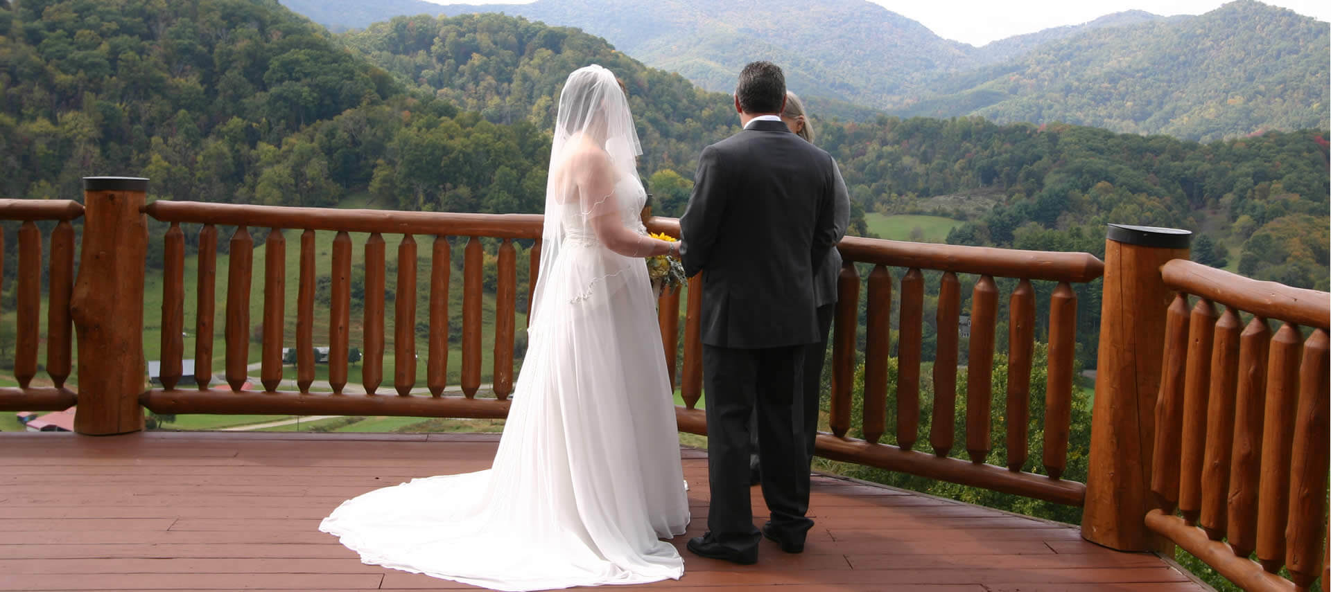 A bride in a white gown and grrom in a black tuxedo say their vows on a deck overlooking wooded hills.