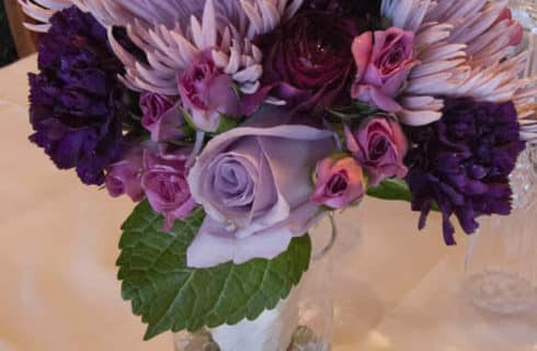 Bouquet of purple and lavender flowers in a glass vase on a white table.
