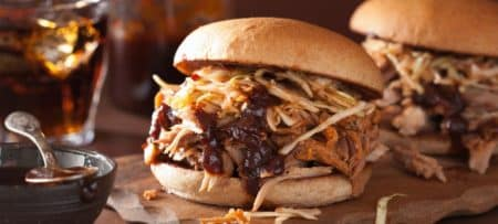 Two heaping burgers filled with BBQ and a refreshing cold drink