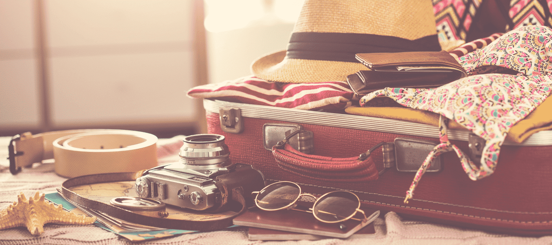 open packed leather suitecase with other miscellaneous items (camera, sunglasses, belt, starfish) sitting in front