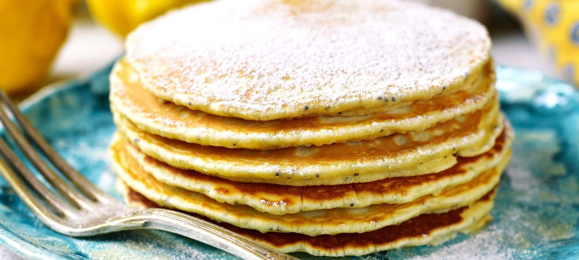 Blue plate topped with a stack of lemon pancakes dusted with powdered sugar