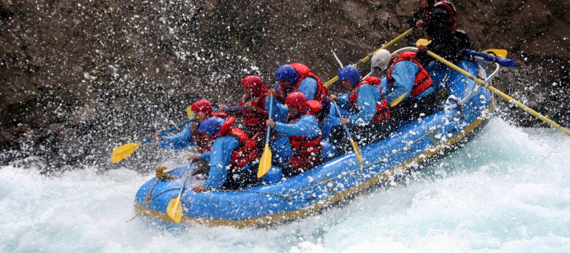 Raft full of people rowing down the rapids surrounded by splashing water
