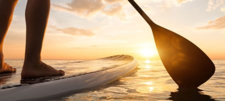 legs of person standing on paddleboard with oar in water facing sunrise glistening off of water
