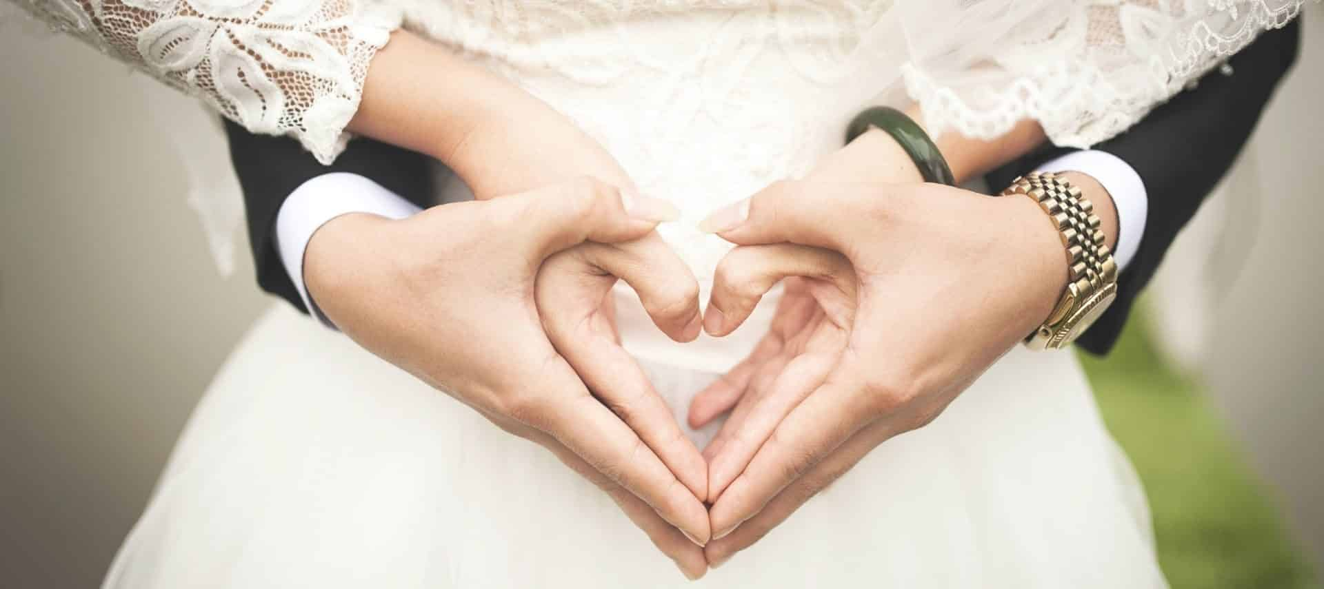 Bride and groom holding hands in heart shape