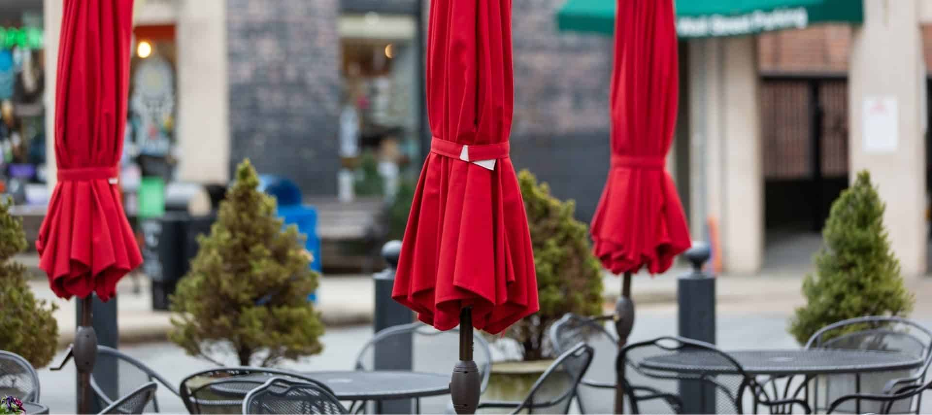 Outdoor dining tables in downtown Asheville with closed red umbrellas