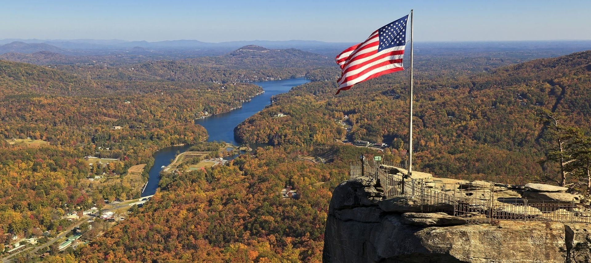 Top of Chimney Rock in NC with flag pole on an rocky outcrop with an aerial view of Asheville and the surrounding area