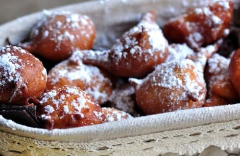 White oval basket full of apple firtters sprinkled with powdered sugar