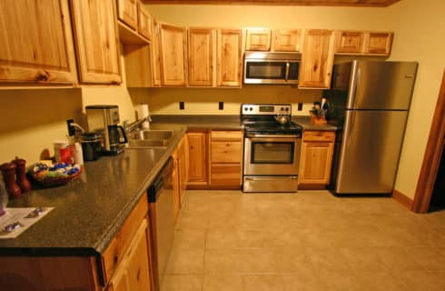 Bright and clean kitchen with a tile floor, stainless appliances and light oak cabinets,