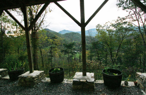 View from rustic porch of the trees and valley below, surrounded by mountains.